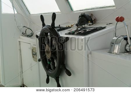 Steering wheel on an old yacht. Captain's cabin.