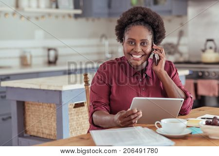 Portrait of a smiling young African woman using a digital tablet and talking on a cellphone while sitting at a table working from home