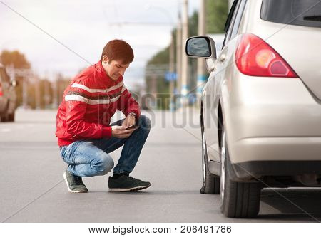 Young caucasian man sitting near broken car and calling to car service. Male driver having troubles with his auto on cityroad