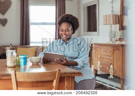 Smiling young African woman sitting at her kitchen table in the morning using a digital tablet and eating a healthy breakfast