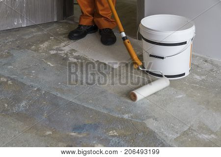Apartment under construction. Worker puts primer with roller on concrete floor