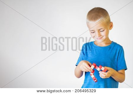 Boy with wooden logical toy. Child playing educational toys.