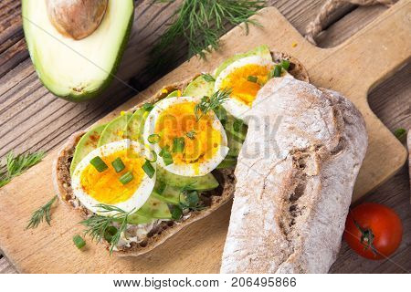 Avocado and egg sandwich on a wooden background. Fresh organic vegetables eggs and whole wheat bread. Healthy breakfast. Rustic style.