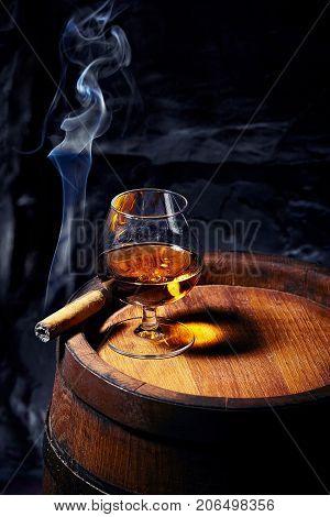 Cognac And Cigar On Old Oak Barrel.blue Stone Background