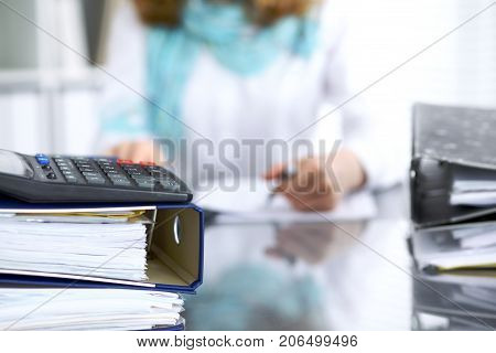 Binders with papers are waiting to be processed with businesswoman or secretary back in blur. Internal Revenue Service inspector checking financial document.