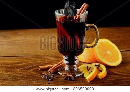 Hot mulled wine glasses with spices canmon sticks, star anise, dried lemon on a wooden table.Vertical shot.Cutted orange.Selective focus.