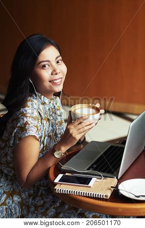 Portrait of female blogger drinking cappucino and working in cafe