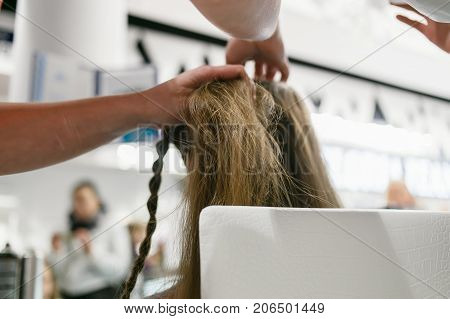 braided pigtails in the beauty salon. Hairstyle