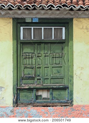 old traditional green painted window with closed shutters with peeling distress and damage on a light yellow wall in spain