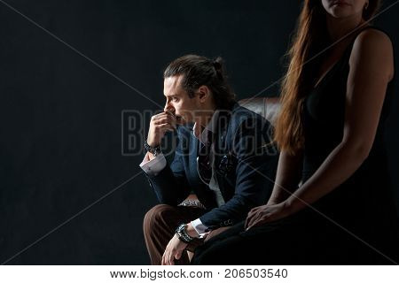The actor or mature man wearing suit in a classical retro fashion style. The stylish man sitting on a leather couch in a studio. The woman standing near