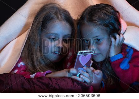 First love and friendship concept. Girls with curious faces. Pyjamas party for children. Girl friends under blanket playing with mobile phone. Kids wearing red jammies in bed on black background.