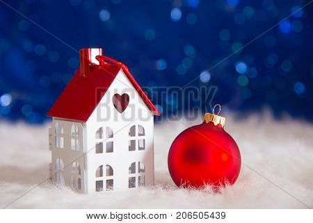 Red Christmas Ball With Toy Little House On White Fur With Garland Lights On Blue Bokeh Background