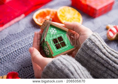Female Hands In Gray Knitted Sweater Holding Green Wooden House On Christmas Decorative Background