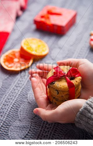 Female Hands In Gray Knitted Sweater Holding Chocolate Cookie On Christmas Decorative Background