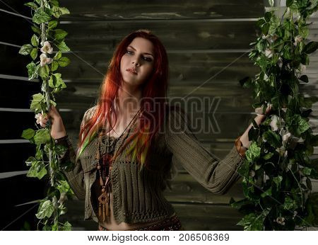 Young hippie boho redhead woman having fun on a swing. Hippie style on a wooden background.