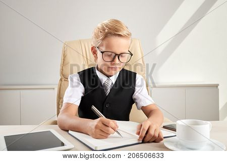 Serious little business executive in glasses writing ideas into textbok