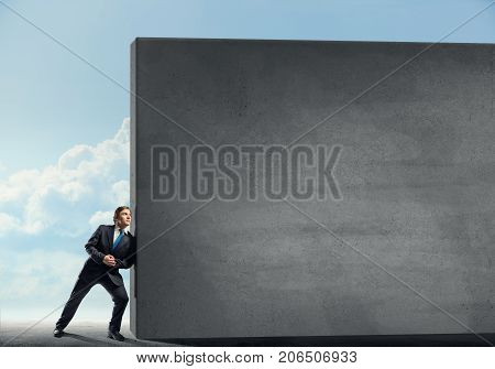 Young businessman making effort to move blank concrete wall poster