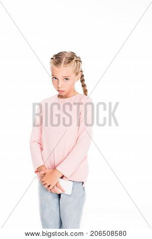 Young child holding smartphone with guilty look on her face isolated on white