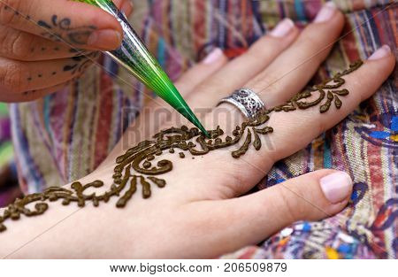Human hand being decorated with henna tattoo
