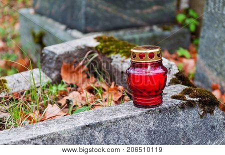 One lonely votive candle standing on tombstone and burning. Stone grave green plants and old plant leaves seen in background