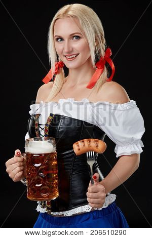 Waitress in traditional german costume holding beer glass on Oktoberfest, black background