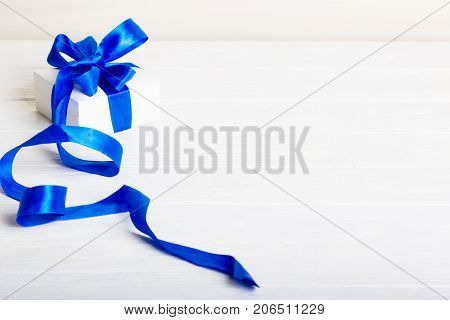 Christmas present gifts box on white wooden background. Gift birthday Christmas present concept - white gift box with blue ribbon on white painted wooden background