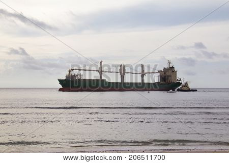 Large freighter and Coastal Patrol boat in the ocean and blue sky. empty freighter. Water transportation.