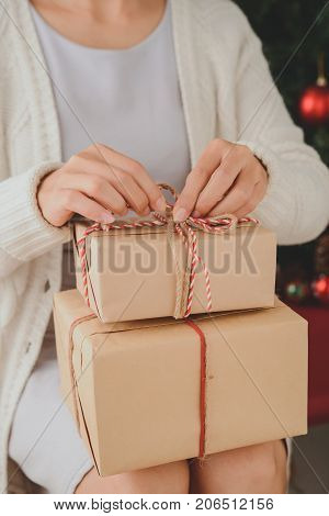 Cropped image of woman unwrapping Christmas presents