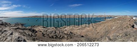 Panoramic view of Luderitz harbor and its rocky landscape with many boats and ships in the lagoon, Namibia, Southern Africa