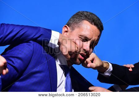 Business conflict and argument concept. Businessman with confused face in formal suit on blue background. Man beaten by coworkers fists in face. Company leaders fight for business leadership