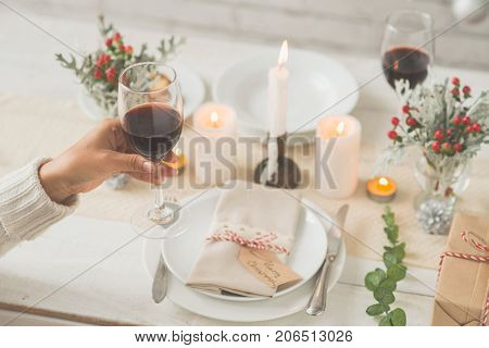Woman drinking red wine on Christmas eve