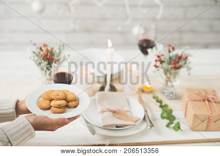 Woman bringing dish with cookies to the Christmas table