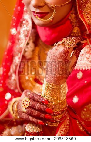Close-up shoot of indian bride wearing elegant bangles and rings in hand at wedding.