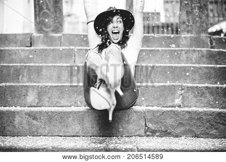 Happy woman having party celebrating her birthday throwing confetti with her hands - Pretty young girl having fun sitting on stairs - Party and celebration concept - black and white editing