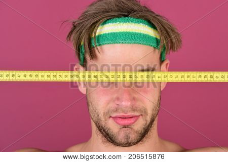 Man With Messy Hair Has Eyes Closed With Measure Tape