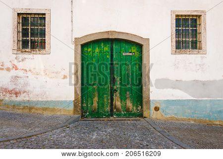 Old garage green door and two windows