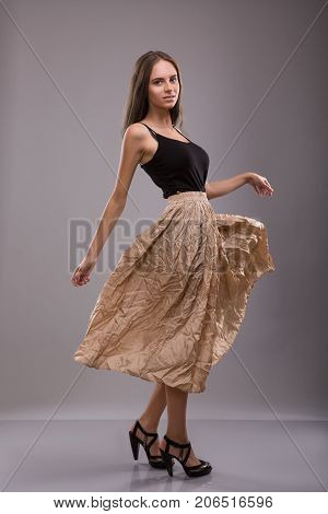 Woman dressing in Spreading skirt staying over gray background. Studio shoot