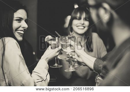 Happy young friends toasting and cheering cocktails at disco bar - Multiracial people having fun enjoying drinks at club - Black and white editing - Focus on glasses