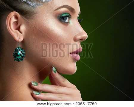 Back view of attractive brunette girl with shiny manicure, makeup in green colors, plump lips, touching neck and chin. Beautiful woman with big rounded earring looking away, showing nails. Studio.