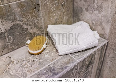 Closeup Of Staging Shower Towel And Brush In Modern Stone Grey Bathroom Seat Bench In Model Home, Ap