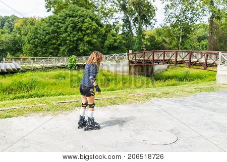 Young woman learning rollerskating or roller skating outside outdoor in summer park with knee and elbow pads by bridge