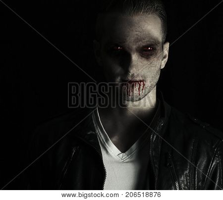 Portrait of an handsome vampire after his transformation on a black background