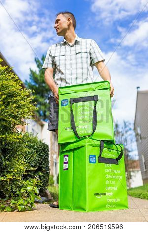 Fairfax USA - September 12 2017: Amazon Fresh insulated grocery delivery bags totes on front home house porch closeup with man looking closing lid