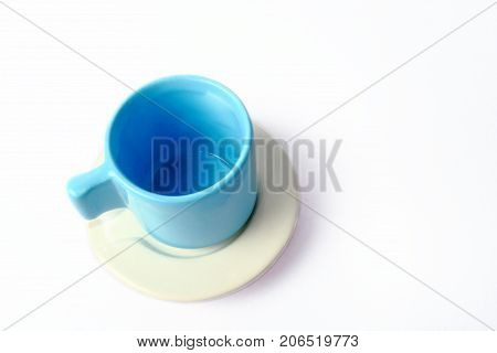 An empty blue cup with white plate isolated on white background.