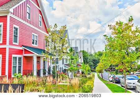 Silver Spring USA - September 16 2017: Colorful multicolored red blue painted residential new townhouses homes houses in Maryland with cars on street in summer