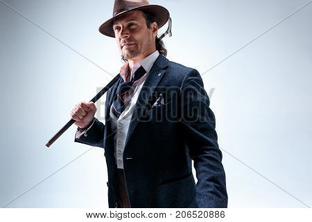 The mature bearded man in a suit and hat holding cane. Isolated on a gray studio background.