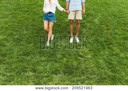 partial view of couple holding hands while walking on green lawn together