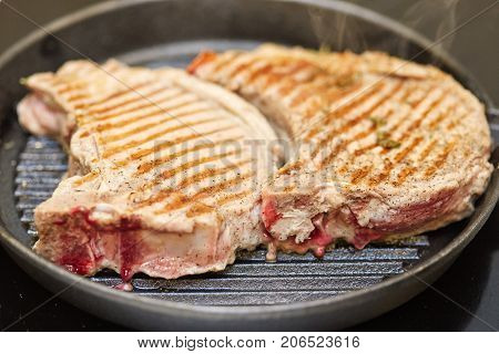 Roasted fresh pork meat steak in a frying grill pan closeup
