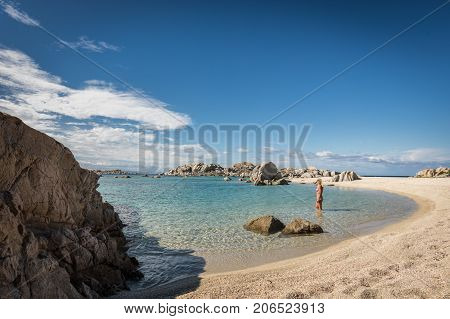 Woman in bikini paddling in the translucent Mediterranean sea just off a deserted sandy beach on Cavallo island near Corsica in France with translucent Mediterranean and blue sky