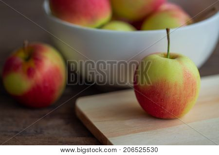 Fuji apple on cutting board put on rustic wood table and stack in white bowl with copy space.Delicious sweet and juicy fuji apple suitable for salad cooking or bakery. Fuji apple has origins in Japan. Prepare apple for cooking or bakery.